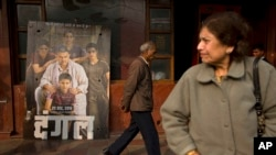An elderly man walks past a poster of Bollywood movie 'Dangal,' a 2016 Bollywood biopic on an Indian wrestling coach and his two professional wrestler daughters, outside a theater in New Delhi, India.