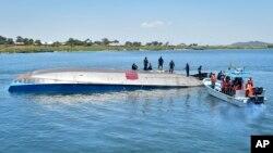 지난 22일 탄자니아 우카라섬 빅토리아 호수에서 전복된 여객선 위로 구조 대원들이 모여 있다.