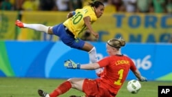 Brazil's Marta (L) leaps over Sweden goalkeeper Hedvig Lindahl as she attempts a shot on goal during a group E match of the women's Olympic football tournament between Sweden and Brazil at the Rio Olympic Stadium in Rio De Janeiro, Brazil, Aug. 6, 2016. B