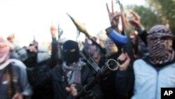 Pria-pria bersenjata di jalanan Fallujah, Irak, meneriakkan slogan-slogan melawan pemerintahan yang dipimpin kelompok Syiah (7/1).