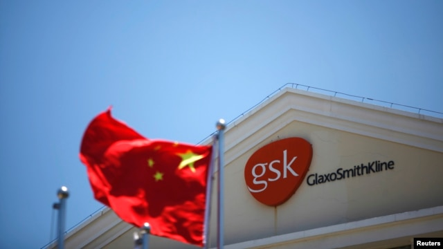 A Chinese national flag flutters in front of a GlaxoSmithKline (GSK) office building in Shanghai, July 12, 2013.