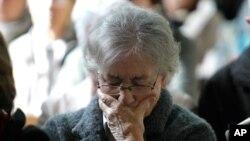 Seorang perempuan menundukkan kepalanya di sebuah kebaktian mengenang para korban jatuhnya pesawat Germanwings. Kebaktian khusus ini berlangsung Notre Dame de Bourg, in Digne-les-Bains (28/3).