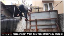 Ảnh chụp màn hình từ video trên YouTube cho thấy người đàn ông này phải leo tường ra vào ngôi nhà mỗi ngày để mua thức ăn.