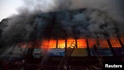 Locals and fire-fighters try to control a fire at a garment factory in Dhaka, March 6, 2014.