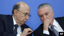 Brazil's acting President Michel Temer, right, talks with his Economy Minister Herinque Meirelles.