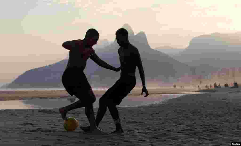 브라질리우데자네이루의 이파네마 해변에서 두 남성이 축구를 하고 있다.