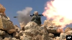 FILE - This frame grab from video released July 22, 2017, and provided by the government-controlled Syrian Central Military Media, shows a Hezbollah fighter firing a rocket-propelled grenade on the Lebanon-Syria border.