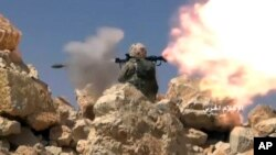 Cuplikan video yang dirilis hari Sabtu, 22 Juli 2017 menunjukkan seorang pejuang Hezbollah menembakkan pelontar granat selama bentrokan dengan militan yang terkait al-Qaida di perbatasan Lebanon-Suriah (foto: Syrian Central Military Media, via AP)