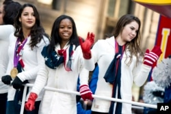 FILE - U.S. gymastics team members, from right, McKayla Maroney, Gabby Douglas and Aly Raisman ride a float in the Macy's Thanksgiving Day Parade in New York, Nov. 22, 2012. All three are among the women who have publicly said they were among Dr. Larry Nassar's abuse victims.