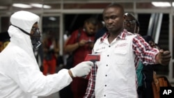 A Nigerian port health official uses a thermometer on a worker at the arrivals hall of Murtala Muhammed International Airport in Lagos, Aug. 6, 2014.