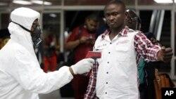 2014年8月6日一名尼日利亞港口檢疫人員為一名在拉各斯入境的旅客測量體溫。
