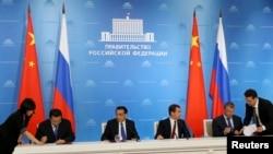 俄罗斯总理梅德韦杰夫和中国总理李克强在莫斯科出席俄罗斯国家石油公司与中国石油天然气集团公司深化战略合作协议的签字仪式。(2014年10月13日)