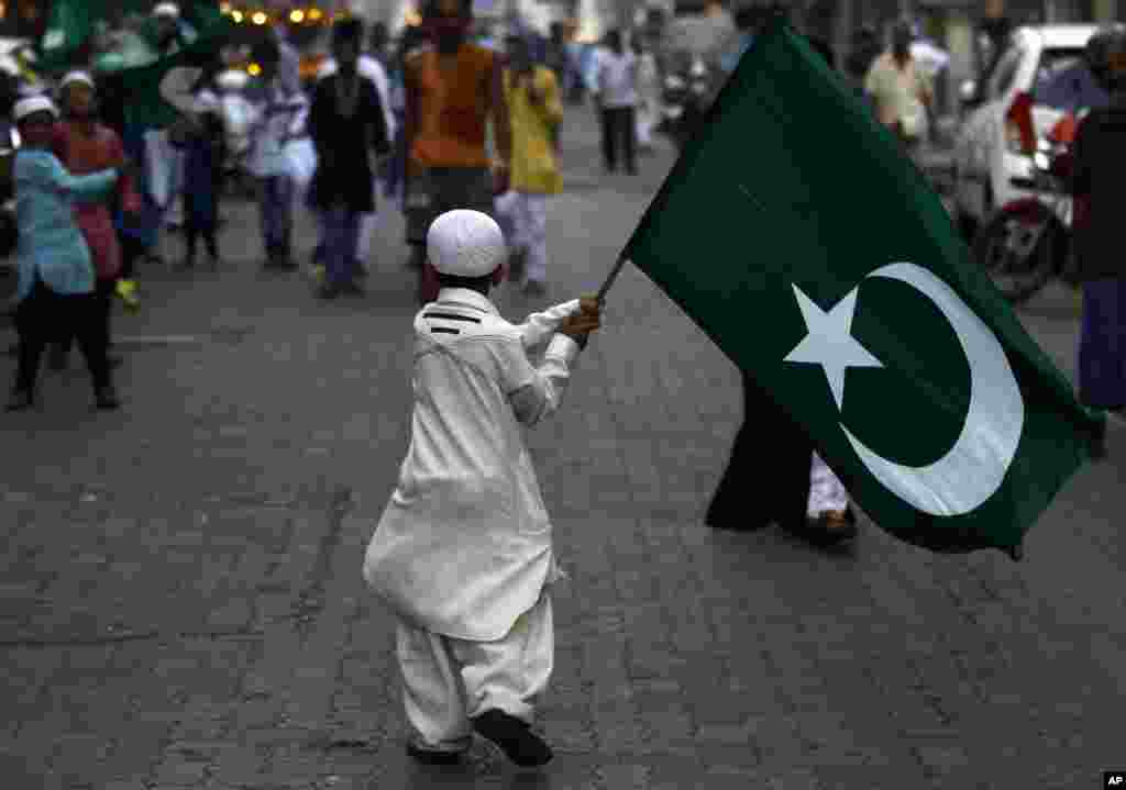 An Indian Muslim boy holds a religious flag and walks in a procession to mark the birth anniversary of Prophet Mohammed in Mumbai.