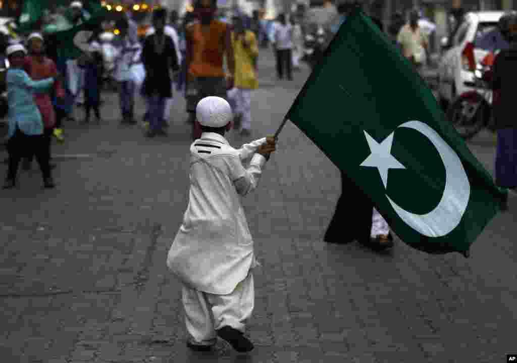 Một cậu bé Ấn Ðộ theo Hồi Giáo cầm lá cờ tôn giáo trong buổi diễn hành tại Mumbai, kỷ niệm sinh nhật của Tiên tri Mohammed. (AP)