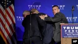 5일 네바다 주 리노에서 열린 유세현장에서 비밀경호국 요원들이 트럼프 후보를 급히 대피시키고 있다.