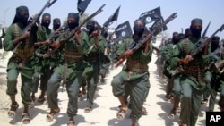 FILE - Al-Shabab fighters are seen marching with their weapons during exercises on the outskirts of Mogadishu, Somalia, Feb. 17, 2011.