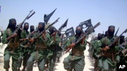 FILE - Al-Shabab fighters are seen marching with their weapons during exercises on the outskirts of Mogadishu, Somalia. Some al-Shabab members are fleeing to the capital and to areas near the border with Kenya because they were overpowered in the region of Middle Juba.