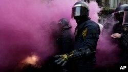 Policías catalanes son envueltos en el humo de las bombas lanzadas por los seguidores de Puigdemont en Barcelona.