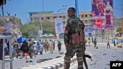 Un membre des services de sécurité somaliens patrouille sur les lieux d'un attentat suicide à la voiture piégée à Mogadiscio, le 30 août 2016.