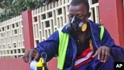 在利比里亞蒙羅維亞市的一名地鐵公司的僱員,在街道上噴灑,企圖以防止致命的伊波拉病毒的蔓延。