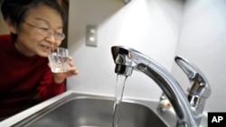 东京的一位妇女在从水龙头中接水
