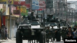 Government soldiers with armored personnel carriers move to reinforce the government forces battling the Moro National Liberation Front (MNLF) rebels in Zamboanga City, southern Philippines, Sept.10, 2013.