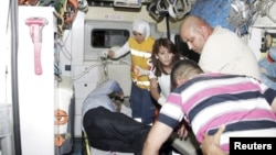 Wounded people are helped onto an ambulance after an explosion in the southeastern Turkish town of Gaziantep, August 20, 2012.