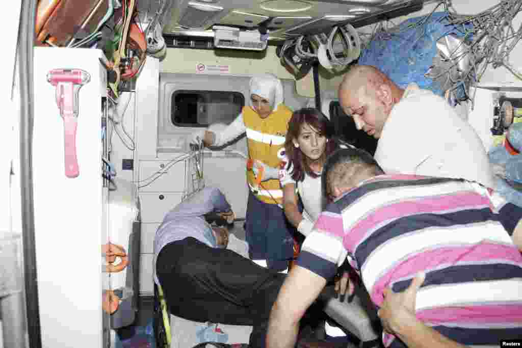 Wounded people are helped onto an ambulance after an explosion in the southeastern Turkish town of Gaziantep August 20, 2012.