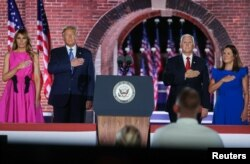 U.S. President Donald Trump, first lady Melania Trump, U.S. Vice President Mike Pence and his wife Karen Pence hold their hands over their hearts as they listen to singer Trace Atkins sing the U.S. National Anthem after Pence's acceptance speech as the 20