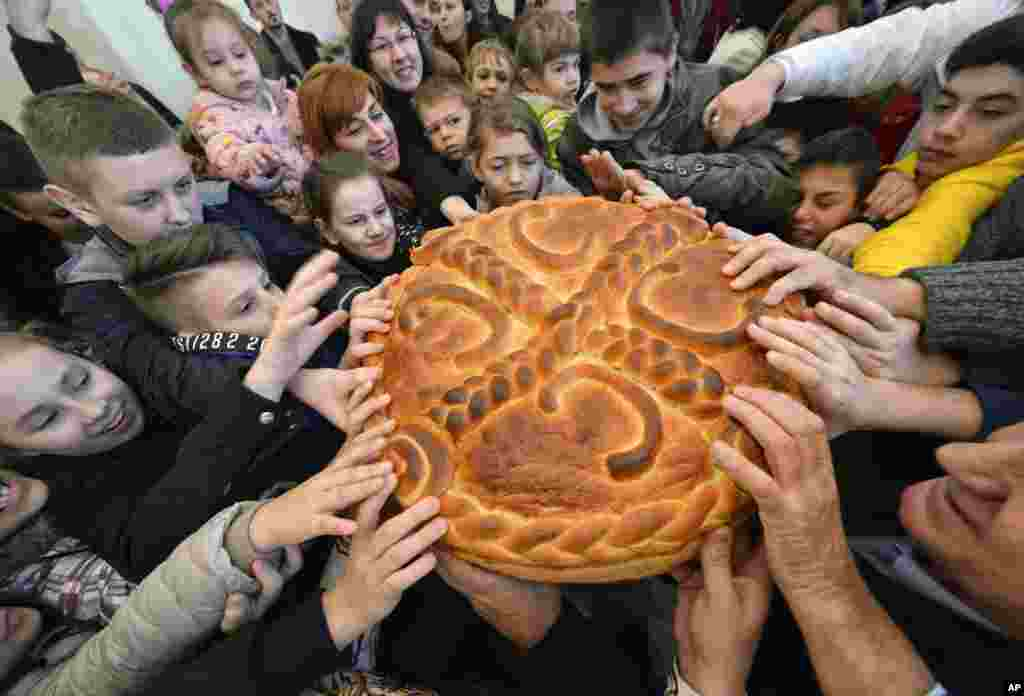Bosnian Serb children prepare to break the traditional Christmas bread to mark Orthodox Christmas Day festivities in Bosnian town of Banja Luka, Bosnia, Jan. 8, 2018.