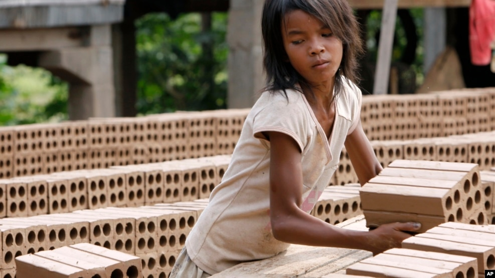 A Cambodian girl prepares bricks to dry under the sun light at a brick factory in Chheuteal village, Kandal province, some 27 kilometers (17 miles) north of Phnom Penh, Cambodia, Monday, May 2, 2011.
