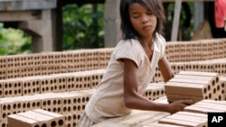 A Cambodian girl prepares bricks to dry under the sun light at a brick factory in Chheuteal village, Kandal province, some 27 kilometers (17 miles) north of Phnom Penh, Cambodia, file photo.