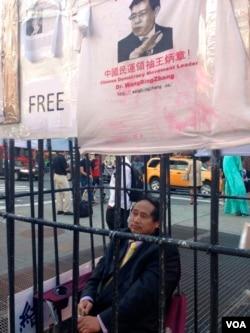 """曾被说成89民运幕后推手的王军涛连续第五天在纽约时代广场参与""""与王炳章同囚""""的行动。(美国之音记者方方拍摄)"""
