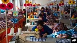 北韓先鋒港紡織廠裡,一排又一批的女工,在縫紉機前忙碌,她們的上方懸掛著塑料向日葵和大型藍色標語。(於2013年11月9日)