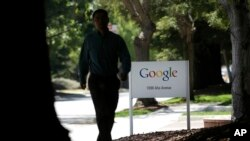 FILE - A man walks past a Google sign in Mountain View, California.