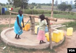 An orphan at the facility pumps water from a borehole that donors helped Mama Susan Tabia drill at the orphanage. (S.P. Apiku/VOA)