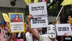Para pendukung Raja Thailand di Bangkok membawa poster yang mengecam campur tangan internasional atas urusan dalam negeri Thailand, terkait hukuman bagi pihak yang dituduh menghina Raja (16/12).