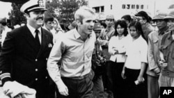 FILE - In this March 14, 1973, file photo, U.S. Navy Lt. Cmdr. John McCain, center, is escorted by Lt. Cmdr. Jay Coupe Jr., to Hanoi, Vietnam's Gia Lam Airport, after McCain was released from captivity. An aide says that McCain died Saturday, Aug. 25, 2018. He was 81. (AP Photo/Horst Faas, File)