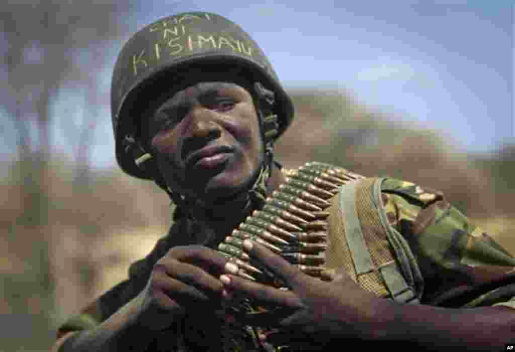 "Kenyan army soldier Nicholas Munyanya, wearing a helmet on which is written in Kiswahili ""Tea in Kismayo"", referring to a key strategic Somali town under the control of al-Shabab, checks his ammunition belt near the town of Dhobley, currently under contro"