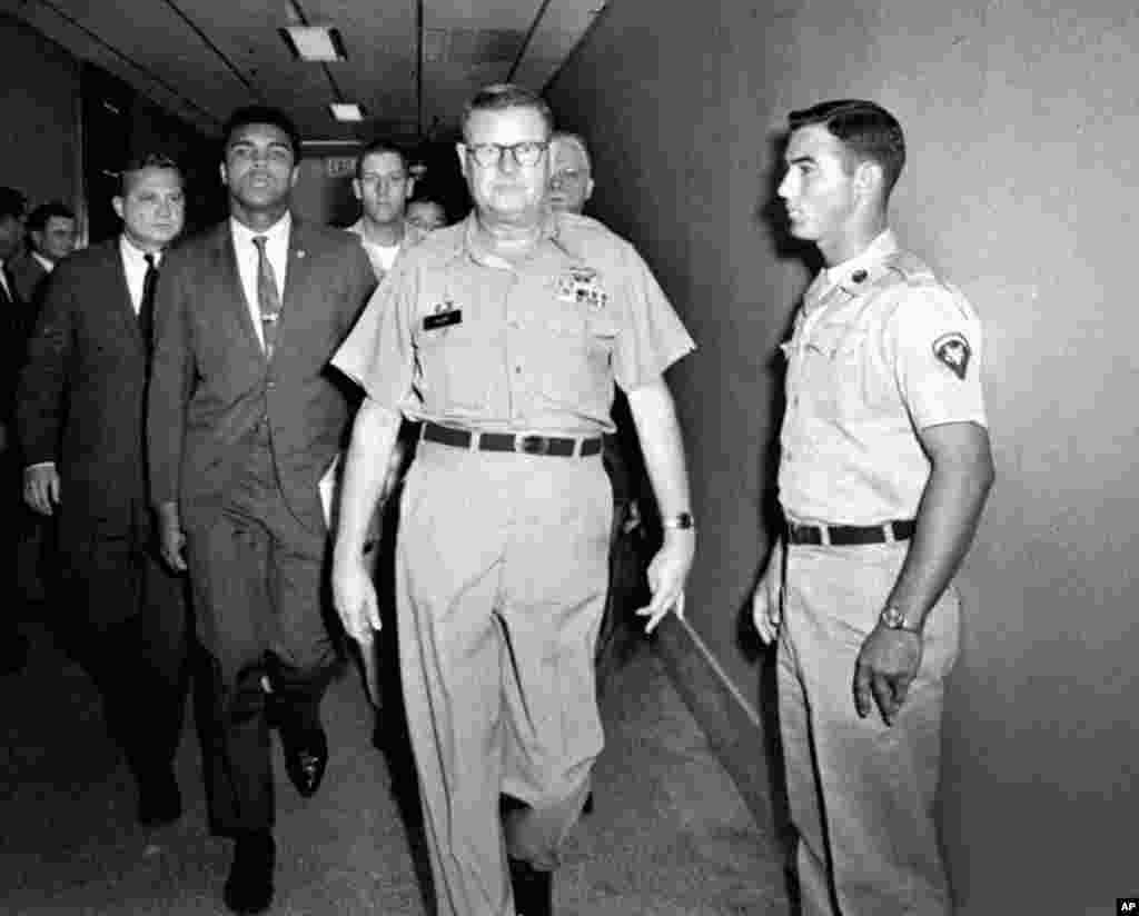 FILE - Heavyweight boxing champion Muhammad Ali is escorted from the Armed Forces Examining and Entrance Station in Houston by Lt. Col. J. Edwin McKee, after Ali refused Army induction, April 28, 1967. Ali died at age 74, June 3, 2016.