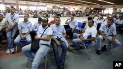 FILE - Workers of General Motors listen during a meeting with government officials at the company's plant in Valencia, Venezuela, April 20, 2017.