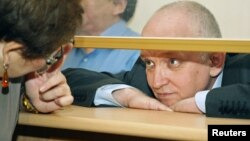Vladimir Kozlov, leader of the unofficial Alga party, looks out from a glass-walled cage during his trial in the Kazakh city of Aktau, October 8, 2012.
