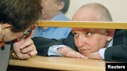 Vladimir Kozlov, leader of the unofficial Alga! party, looks out from a glass-walled cage during his trial in the Kazakh city of Aktau, October 8, 2012.