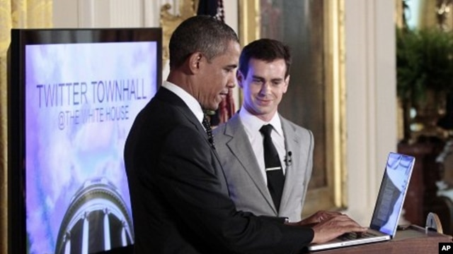 President Barack Obama types during his live-tweet as Twitter co-founder and Executive Chairman Jack Dorsey looks on during the first-ever Twitter Town Hall,  July 6, 2011, in the East Room of the White House
