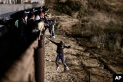 FILE - A migrant jumps the border fence to get into the U.S. side to San Diego, Calif., from Tijuana, Mexico, Jan. 1, 2019.