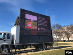 A large-screen TV showing young immigrants' stories is part of Dream Act Central, a space on the National Mall in Washington where immigration activists are pushing for legislative action to replace DACA, Dec. 13, 2017. (A. Barros/VOA)