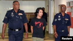FILE - Activist Adam Adli is escorted by police at a courthouse in Kuala Lumpur.