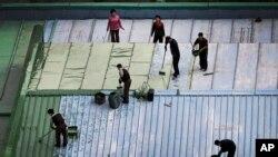 지난달 25일 북한 평양 시내의 한 식당에서 북한 근로자들이 지붕을 페인트칠하고 있다.