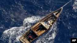 A boat is towed by Japanese coast guard patrol vessel (not pictured) after it was found carrying nine people off the coast of Noto Peninsula, in northwestern Japan, September 13, 2011.
