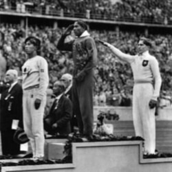 Jesse Owens, center, salutes during the presentation of his gold medal for the long jump, after defeating Nazi Germany's Lutz Long, right, during the 1936 Summer Olympics in Berlin. Naoto Tajima of Japan, left, placed third.